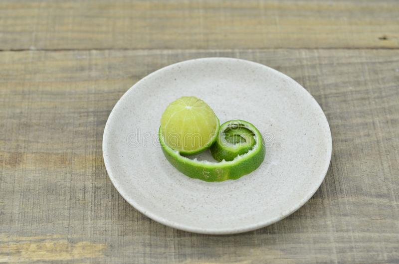 Φρέσκια φλούδα λεμονιών στο πιάτο στο ξύλινο υπόβαθρο στοκ εικόνες με δικαίωμα ελεύθερης χρήσης