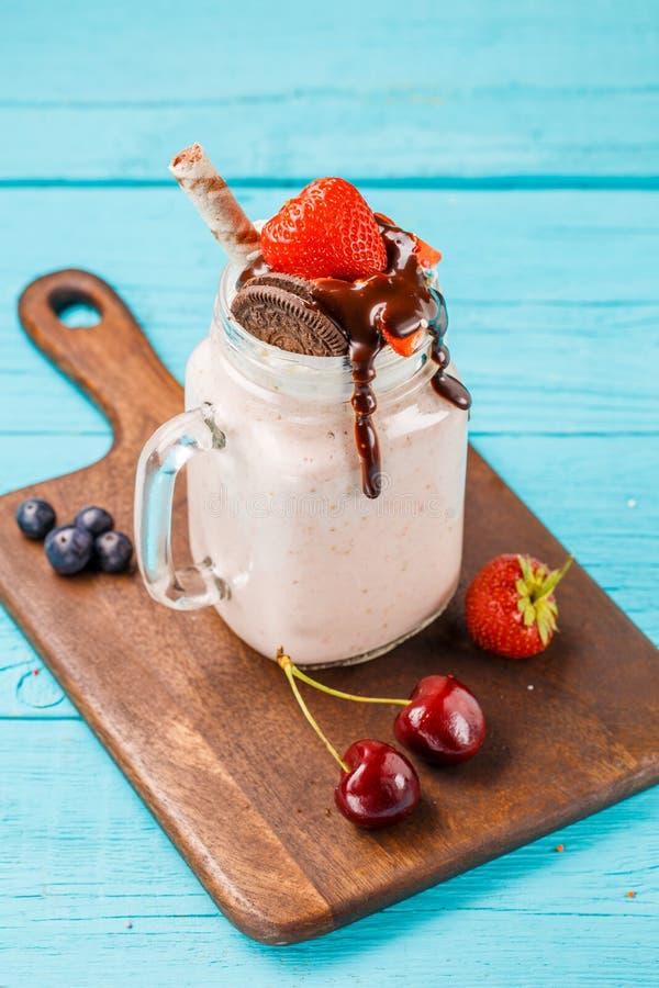 Φρέσκια φράουλα milkshake και μούρα στο ξύλινο γραφείο στον μπλε πίνακα στοκ φωτογραφία με δικαίωμα ελεύθερης χρήσης