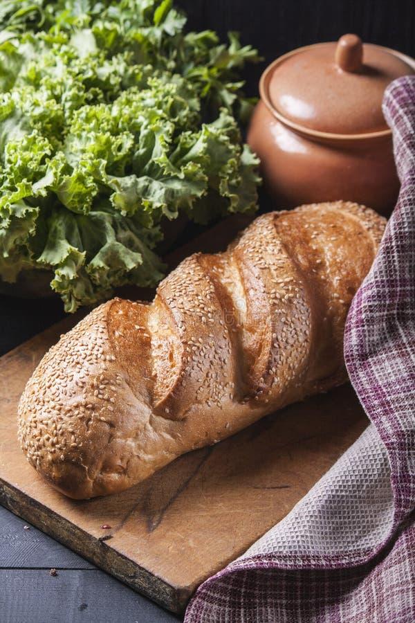 Φρέσκια φραντζόλα που ψεκάζεται με τους σπόρους σουσαμιού σε έναν ξύλινο πίνακα Εύγευστο ψήσιμο στοκ φωτογραφία