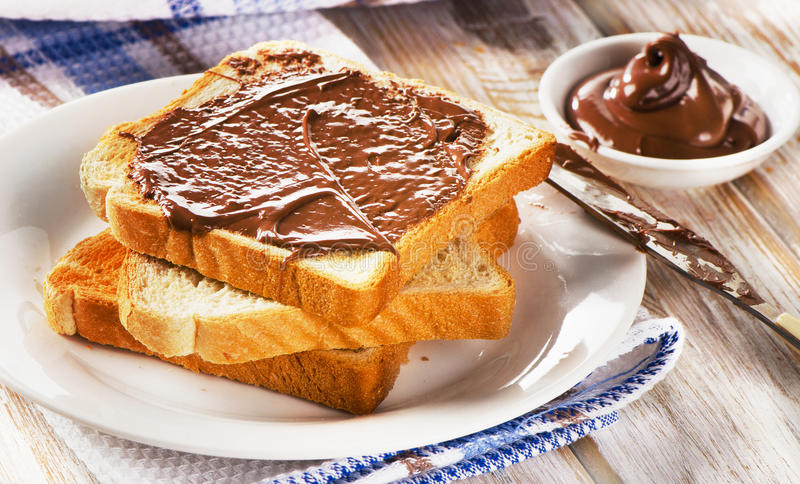 Φρέσκια φρυγανιά με τη σοκολάτα που διαδίδεται σε ένα άσπρο πιάτο στοκ φωτογραφία