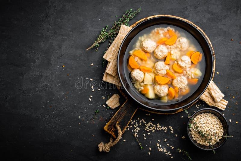 Φρέσκια φυτική σούπα με τα κεφτή και κριθάρι μαργαριταριών στο κύπελλο στο μαύρο υπόβαθρο στοκ εικόνες