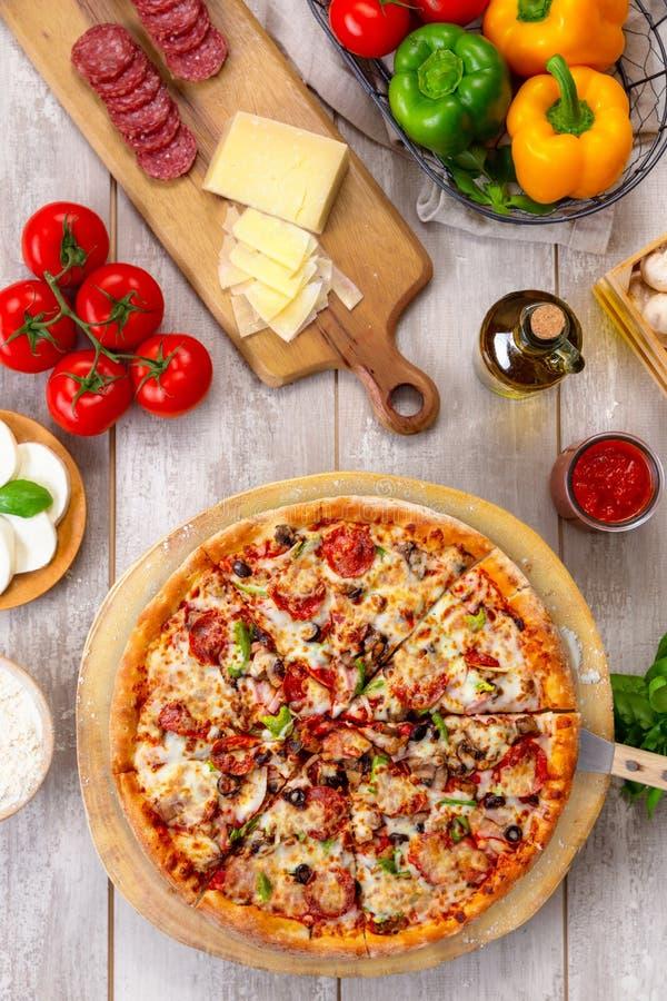 Φρέσκια ψημένη ανώτατη πίτσα στον ξύλινο πίνακα και τον πίνακα, με τα ζωηρόχρωμα χορτοφάγα συστατικά, την κάθετη υπερυψωμένη τοπ  στοκ εικόνες