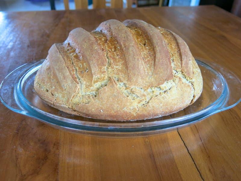 Φρέσκια ψημένη φραντζόλα του ψωμιού σε έναν δίσκο γυαλιού Οργανική τροφή και ζύμη Υγιή τρόφιμα που προετοιμάζονται για τη σπιτική στοκ φωτογραφία