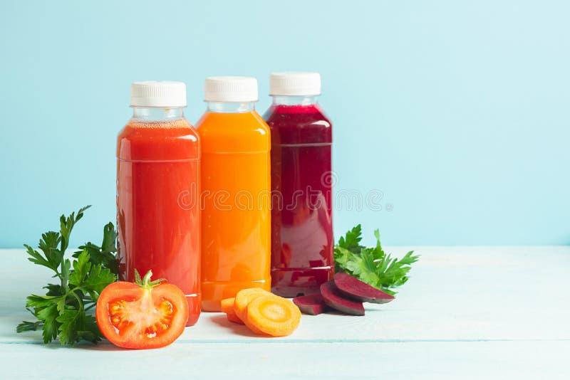 Φρέσκοι καταφερτζήδες χυμού από ποικίλα τεύτλα ντοματών μήλων καρότων λαχανικών στα μπουκάλια σε ένα ξύλινο μπλε υπόβαθρο στοκ εικόνα