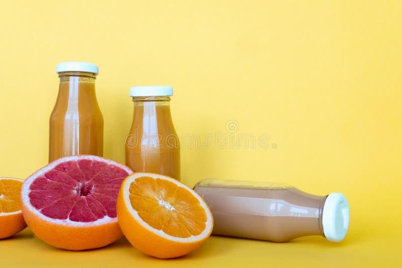 Φρέσκοι χυμοί πορτοκαλιών και γκρέιπφρουτ με τα φρούτα, που απομονώνονται στο κίτρινο υπόβαθρο r στοκ εικόνες με δικαίωμα ελεύθερης χρήσης