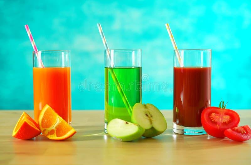 Φρέσκοι χυμοί πορτοκαλιών, μήλων και ντοματών με τη διακόσμηση τμημάτων νωπών καρπών στοκ εικόνα με δικαίωμα ελεύθερης χρήσης