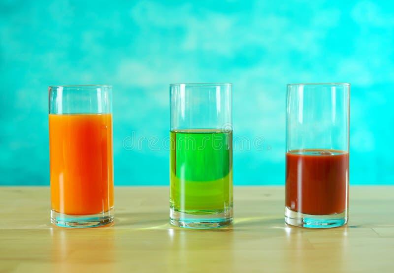 Φρέσκοι χυμοί πορτοκαλιών, μήλων και ντοματών στα γυαλιά στοκ εικόνες