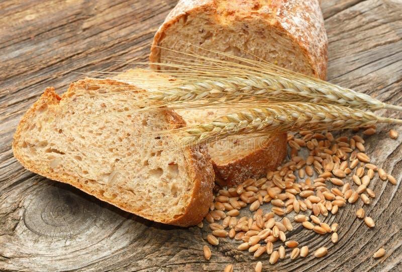 Φρέσκοι ψωμί και σίτος στο ξύλινο υπόβαθρο στοκ εικόνα