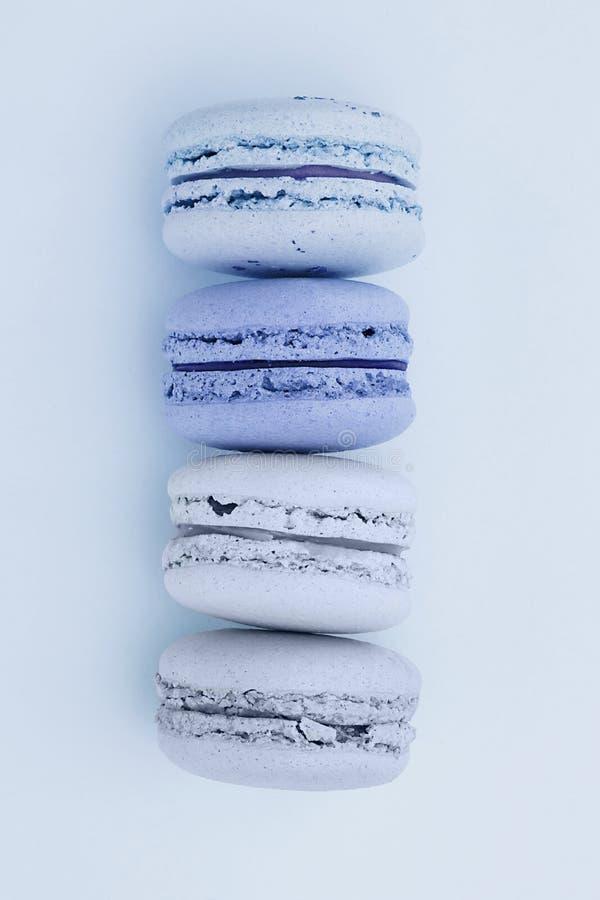 Φρέσκος μπλε-που χρωματίζεται macarons σε ένα επίπεδο βάζει το μπλε υπόβαθρο Σκιές των μπλε χρωμάτων Γαλλικό επιδόρπιο στοκ εικόνα