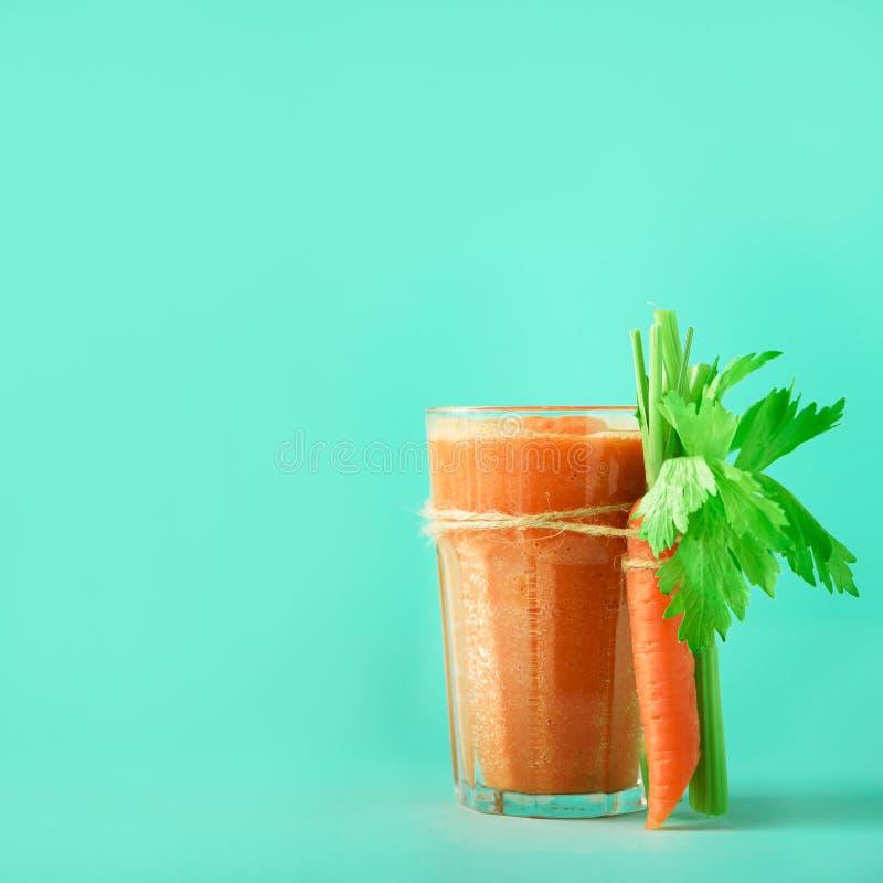 Φρέσκος οργανικός χυμός καρότων με τα καρότα, σέλινο στο μπλε υπόβαθρο Τετραγωνική συγκομιδή Φυτικό smothie στο γυαλί απαγορευμέν στοκ εικόνες
