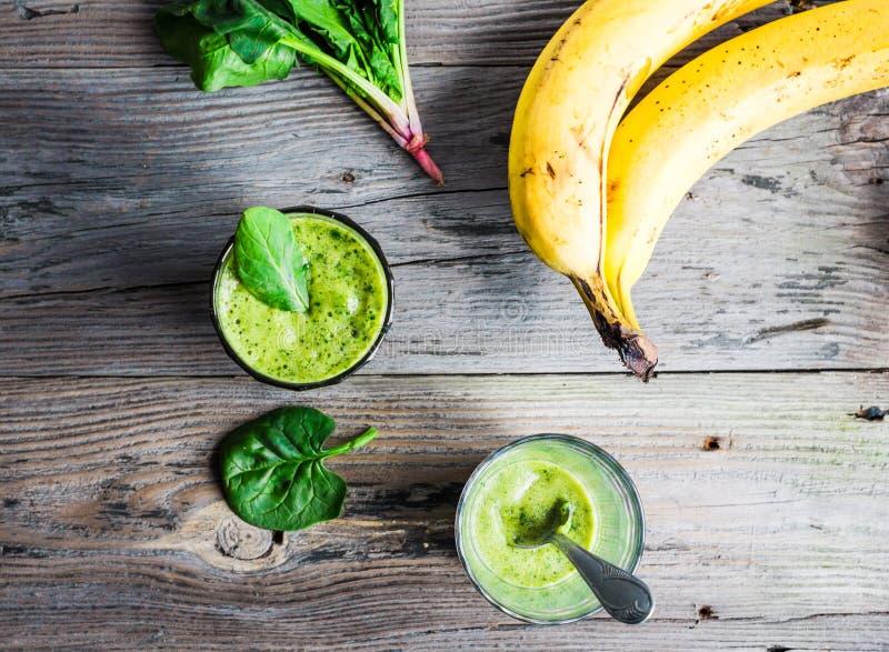 Φρέσκος, πράσινος καταφερτζής βιταμινών με το σπανάκι, μπανάνα σε ένα γυαλί στοκ φωτογραφίες