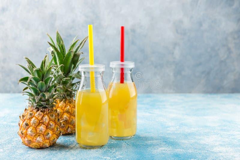 Φρέσκος χυμός ανανά και ώριμος ανανάς στο γκρίζο υπόβαθρο στοκ φωτογραφίες