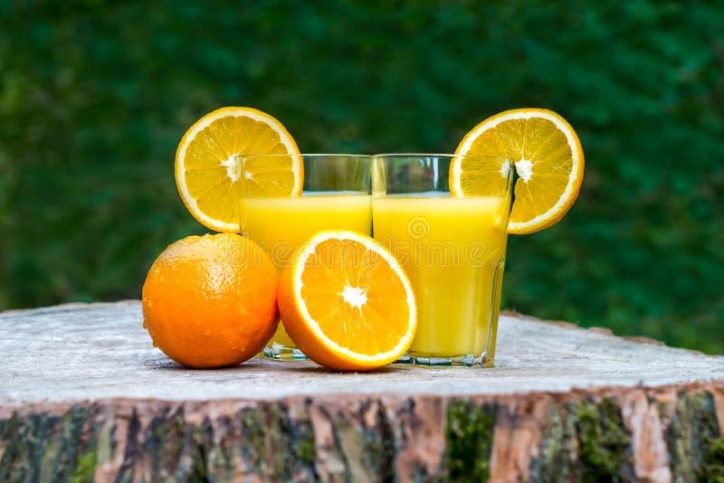 Φρέσκος χυμός από πορτοκάλι με τα φρούτα πορτοκαλιών υπαίθρια στοκ φωτογραφία
