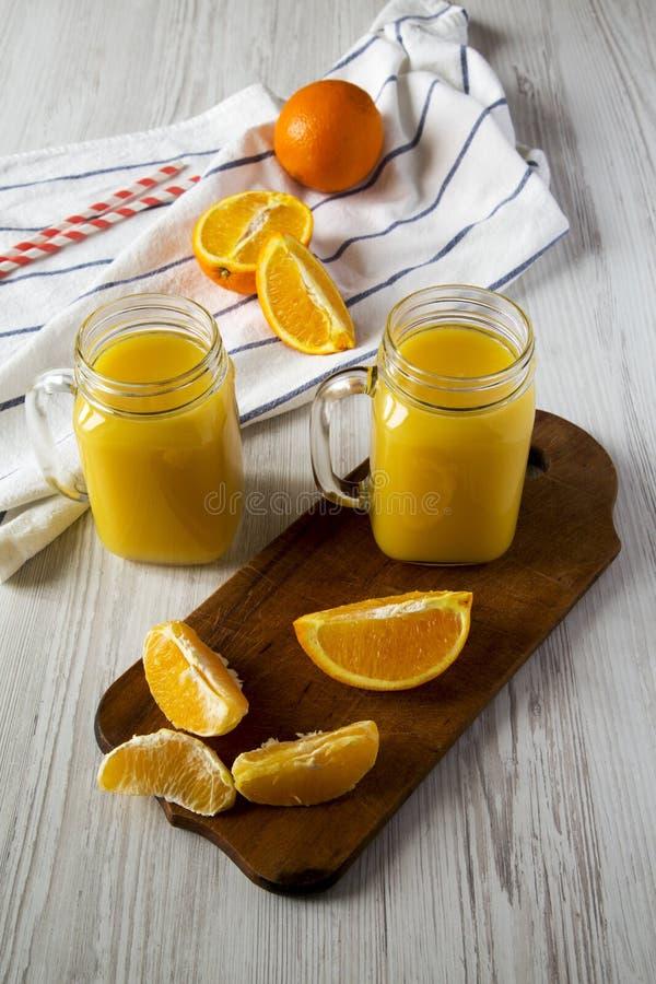 Φρέσκος χυμός από πορτοκάλι στα βάζα γυαλιού πέρα από το άσπρο ξύλινο υπόβαθρο, χαμηλή άποψη γωνίας closeup στοκ εικόνα