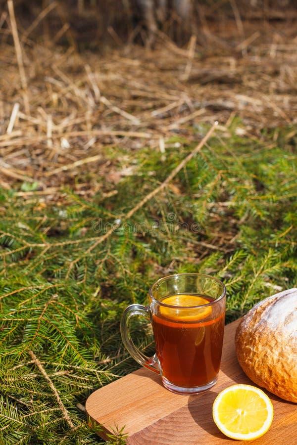 Φρέσκο άσπρο ψωμί σε έναν πίνακα κοπής και κόκκινο τσάι με το λεμόνι στοκ εικόνες