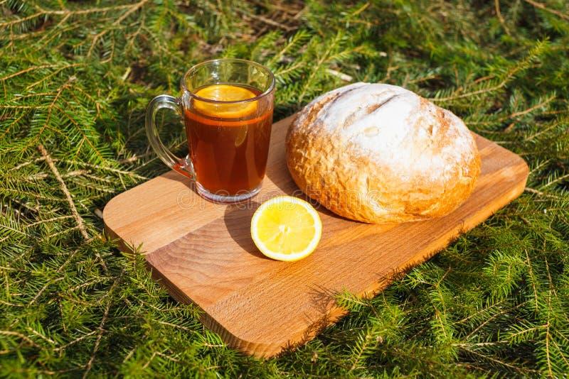 Φρέσκο άσπρο ψωμί σε έναν πίνακα κοπής και κόκκινο τσάι με το λεμόνι στοκ φωτογραφία με δικαίωμα ελεύθερης χρήσης