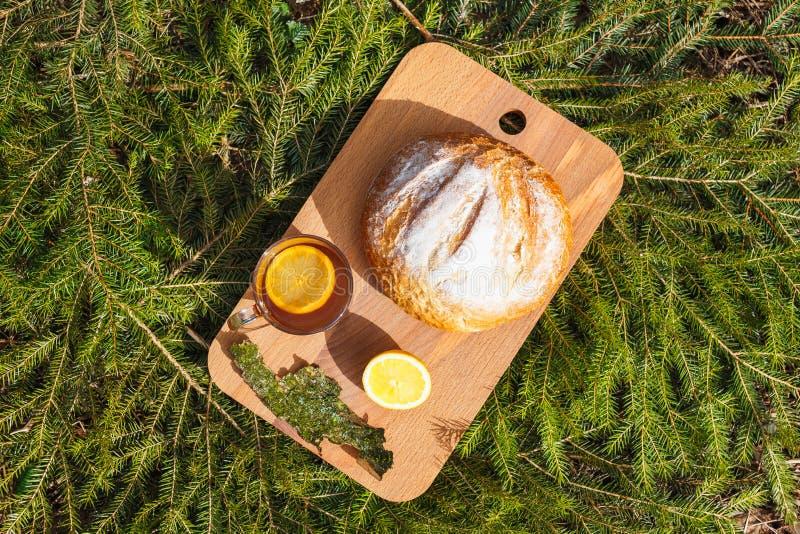 Φρέσκο άσπρο ψωμί σε έναν πίνακα κοπής και κόκκινο τσάι με το λεμόνι στοκ εικόνα με δικαίωμα ελεύθερης χρήσης