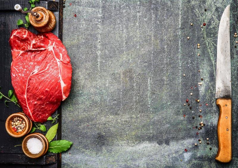 Φρέσκο ακατέργαστο κρέας για BBQ σχαρών ή μαγείρεμα στον πίνακα κουζινών με τα καρυκεύματα και το μαχαίρι κρέατος στοκ εικόνα