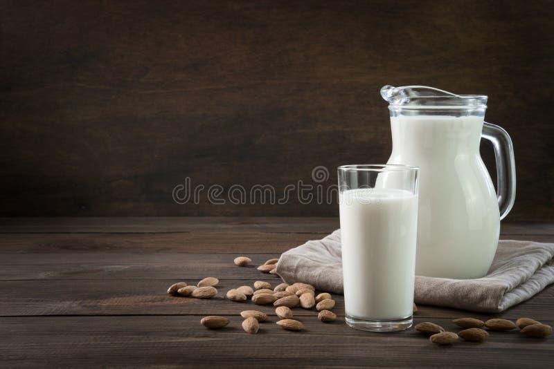 Φρέσκο γάλα αμυγδάλων στο γυαλί και στάμνα στο σκοτεινό ξύλινο πίνακα r στοκ εικόνες με δικαίωμα ελεύθερης χρήσης