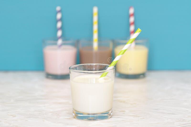 Φρέσκο γάλα μπροστά από μια σειρά αρωματικός milkshakes στοκ εικόνα με δικαίωμα ελεύθερης χρήσης