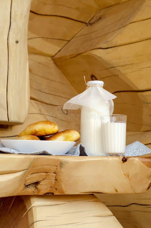 Φρέσκο γάλα σε ένα μπουκάλι γυαλιού και ένα γυαλί, δίπλα στις πίτες σε έναν ξύλινο πίνακα Η έννοια των υγιών οργανικών προϊόντων  στοκ φωτογραφίες