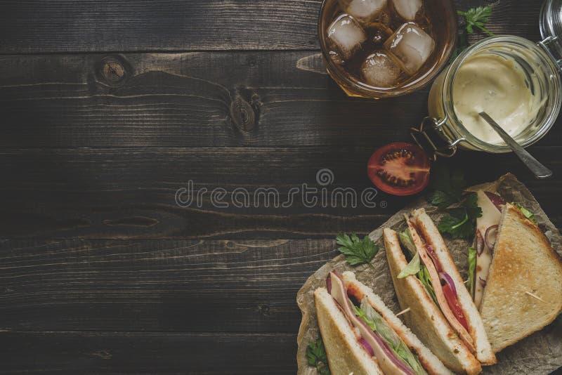 Φρέσκο εύγευστο σάντουιτς, σάλτσες και ποτό λεσχών στην ξύλινη DA στοκ εικόνες