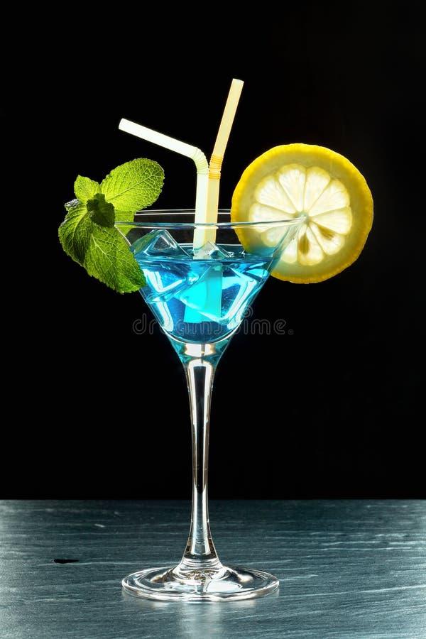 Φρέσκο θερινό κοκτέιλ με το μπλε Κουρασάο, τον πάγο, τα φύλλα μεντών, φέτα λεμονιών και δύο άχυρα αναδρομικά φωτισμένους στο μαύρ στοκ φωτογραφίες με δικαίωμα ελεύθερης χρήσης
