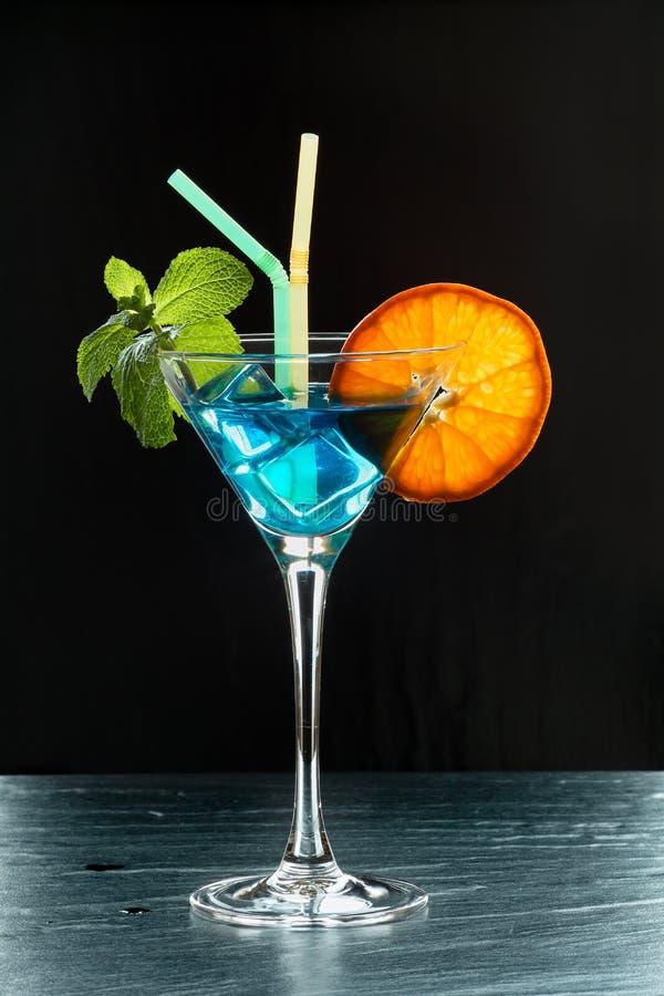 Φρέσκο θερινό κοκτέιλ με το μπλε Κουρασάο, τον πάγο, τα φύλλα μεντών, πορτοκαλιά φέτα και δύο άχυρα αναδρομικά φωτισμένους στο μα στοκ εικόνα με δικαίωμα ελεύθερης χρήσης
