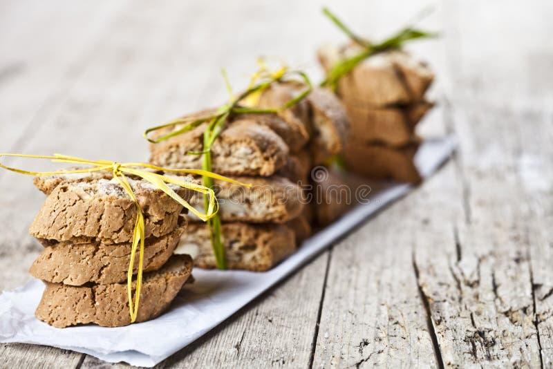 Φρέσκο ιταλικό cantuccini μπισκότων με τους σωρούς σπόρων αμυγδάλων στη Λευκή Βίβλο για το ructic ξύλινο επιτραπέζιο υπόβαθρο στοκ φωτογραφίες