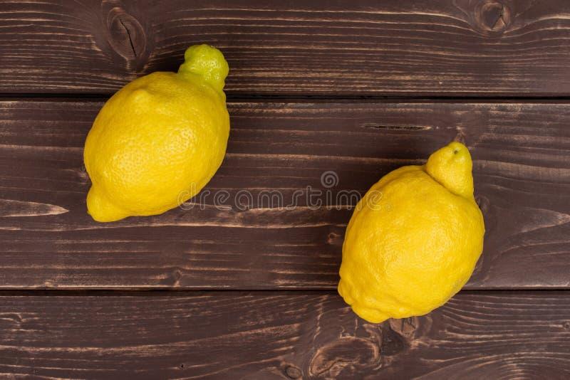 Φρέσκο κίτρινο λεμόνι στο καφετί ξύλο στοκ εικόνες
