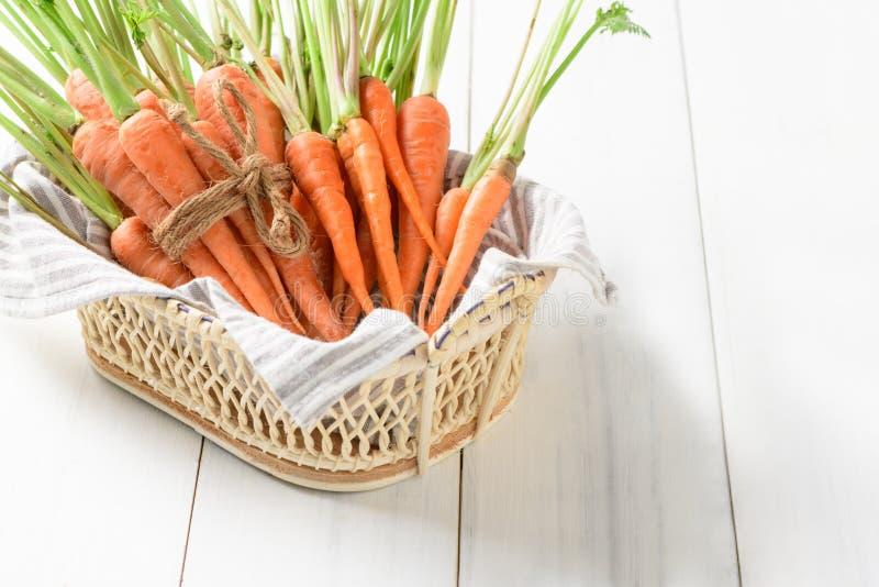 Φρέσκο καρότο, καρότο μωρών στο καλάθι στο άσπρο ξύλινο υπόβαθρο στοκ φωτογραφία