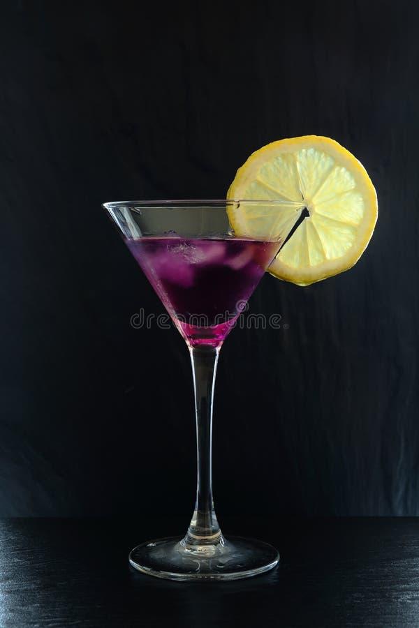 Φρέσκο κοκτέιλ θερινής πορφυρό βροχής σε ένα martini γυαλί με τις φέτες λεμονιών σε μια αναδρομικά φωτισμένη μαύρη κατασκευασμένη στοκ εικόνες