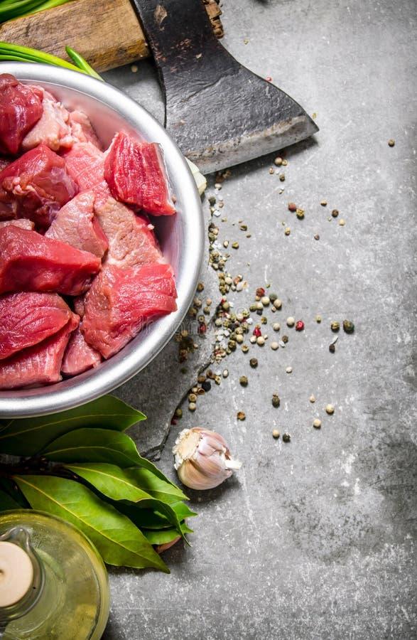Φρέσκο κρέας που τεμαχίζεται με το τσεκούρι και τα καρυκεύματα στοκ εικόνες