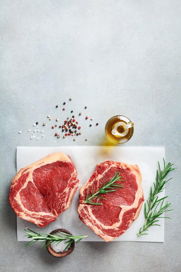 Φρέσκο κρέας στην άποψη επιτραπέζιων κορυφών κουζινών Ακατέργαστα μπριζόλα και καρυκεύματα βόειου κρέατος για το μαγείρεμα στοκ φωτογραφία