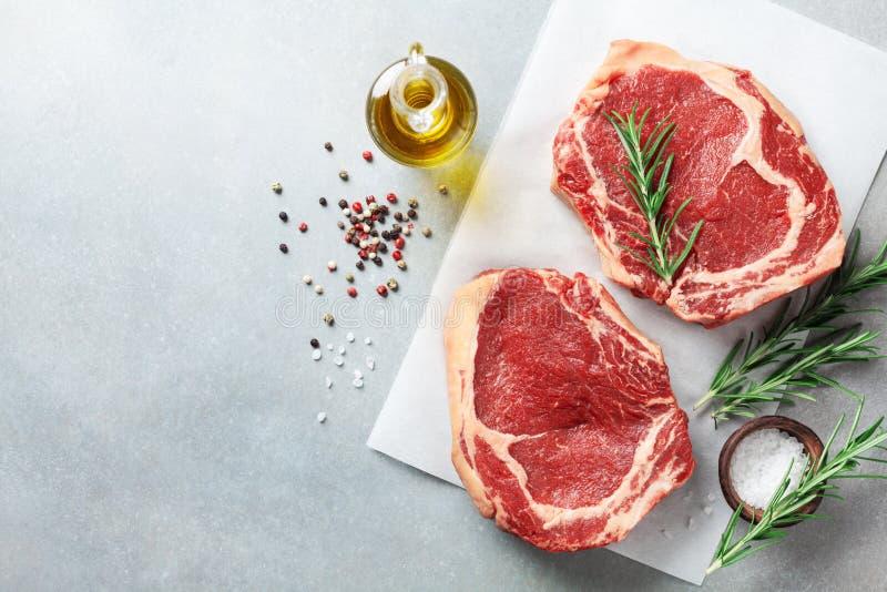 Φρέσκο κρέας στην άποψη επιτραπέζιων κορυφών κουζινών Ακατέργαστα μπριζόλα και καρυκεύματα βόειου κρέατος για το μαγείρεμα στοκ εικόνα