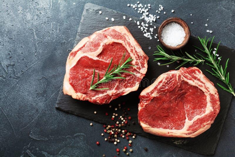Φρέσκο κρέας τοπ άποψη πινάκων πλακών στη μαύρη Ακατέργαστα μπριζόλα και καρυκεύματα βόειου κρέατος για το μαγείρεμα στοκ φωτογραφίες με δικαίωμα ελεύθερης χρήσης