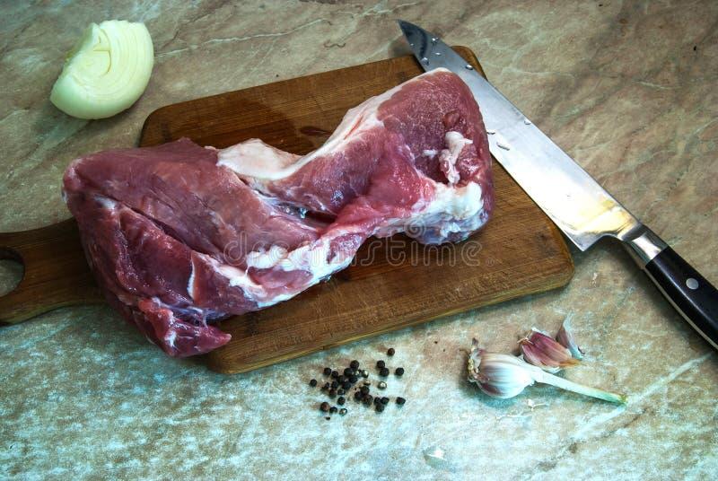 Φρέσκο κρέας χοιρινού κρέατος σε ένα σκοτεινό υπόβαθρο έτοιμο να τεμαχίσει στοκ εικόνα