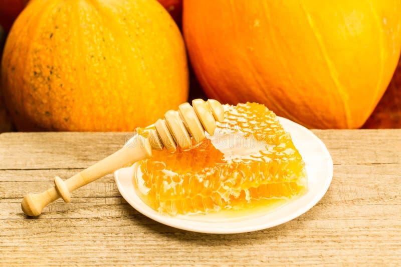 Φρέσκο μέλι στο ξύλινο υπόβαθρο Ύφος φθινοπώρου, κηρήθρα, κολοκύθα στοκ εικόνες