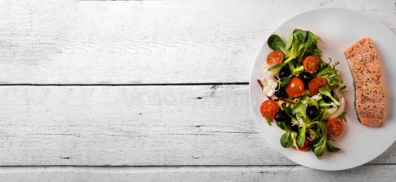 Φρέσκο μίγμα σαλάτας με την ψημένη στη σχάρα λωρίδα σολομών στον άσπρο ξύλινο πίνακα στοκ εικόνες
