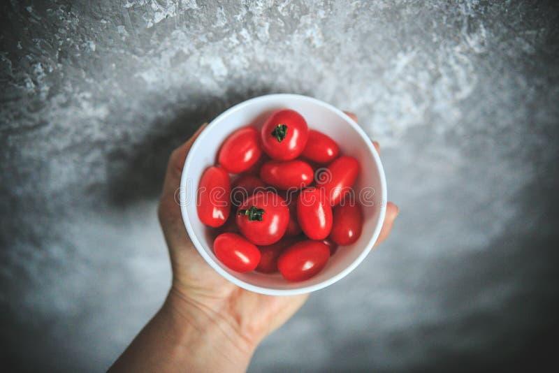 Φρέσκο να φανεί ντομάτες κερασιών στο κύπελλο, κρατώντας υπό εξέταση στο γκρίζο και άσπρο υπόβαθρο που λαμβάνεται από την κορυφή στοκ φωτογραφίες