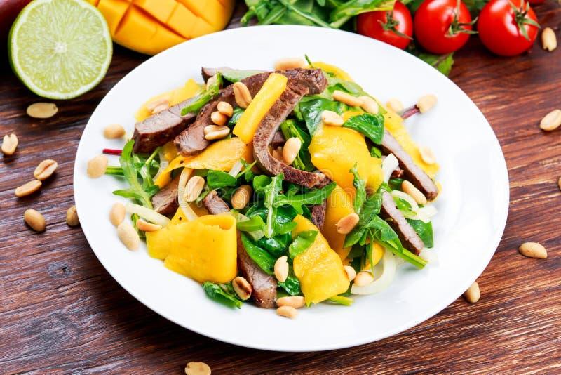 Φρέσκο νόστιμο μάγκο, σαλάτα βόειου κρέατος με τα λαχανικά και τα καρύδια στοκ εικόνες