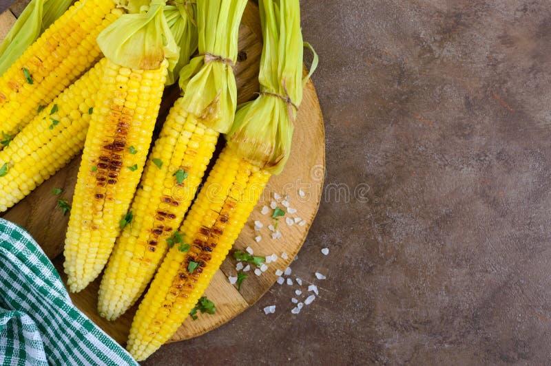 Φρέσκο νόστιμο ψημένο στη σχάρα γλυκό καλαμπόκι με το βούτυρο, το άλας θάλασσας και το cilantro στοκ φωτογραφίες