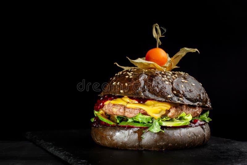 Φρέσκο νόστιμο burger στη μαύρη πλάκα, που διακοσμείται με Physalis στοκ εικόνες με δικαίωμα ελεύθερης χρήσης