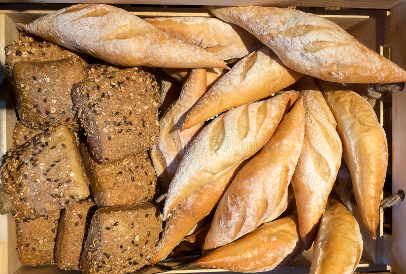 Φρέσκο ολόκληρο ψωμί σίτου στην ξύλινη σύσταση υποβάθρου καλαθιών, τοπ άποψη στοκ εικόνες