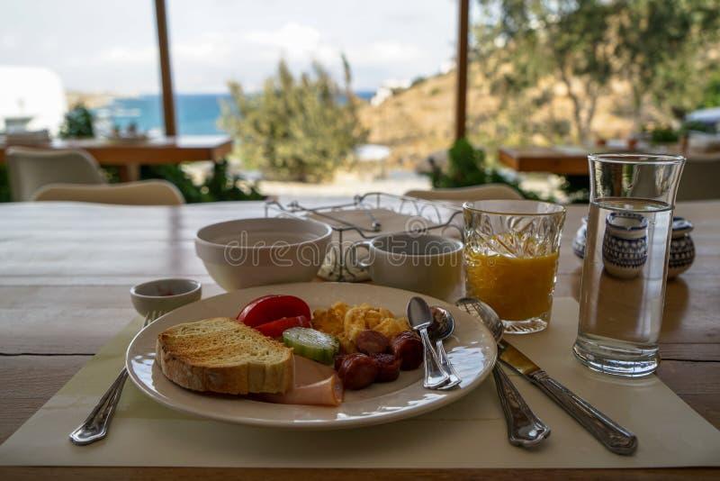 Φρέσκο πιάτο προγευμάτων στον ξύλινο πίνακα συμπεριλαμβανομένης της ομελέτας, του λουκάνικου, του ζαμπόν, της ντομάτας, του αγγου στοκ εικόνα