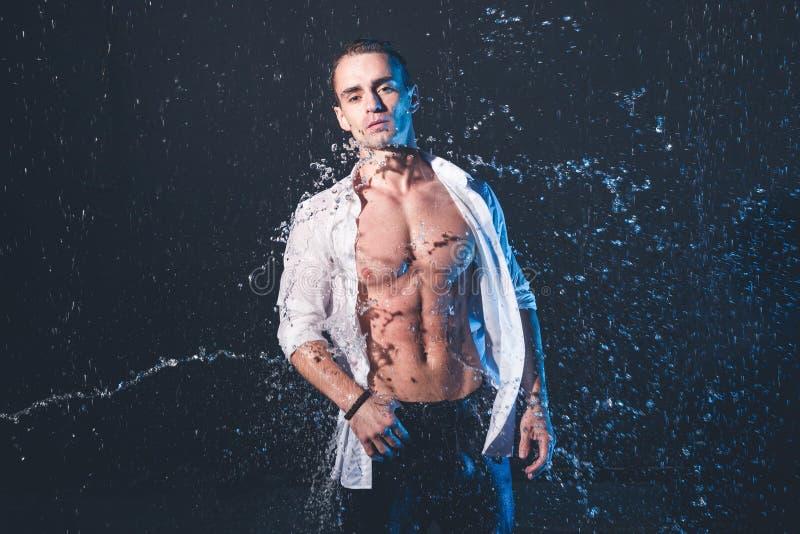 Φρέσκο πορτρέτο του μυϊκού ατόμου με τους παφλασμούς νερού στο σκοτεινό υπόβαθρο στοκ φωτογραφία