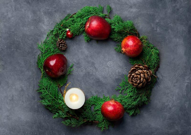 Φρέσκο πράσινο κιβώτιο δώρων κεριών σφαιρών κώνων πεύκων ροδιών μήλων ιουνιπέρων κόκκινο στοκ εικόνες