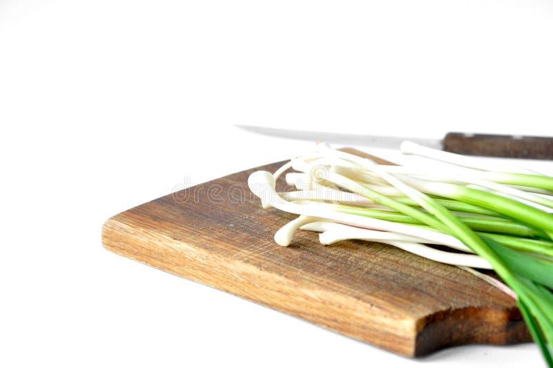 Φρέσκο πράσινο σκόρδο στον πίνακα με ένα μαχαίρι στοκ φωτογραφία με δικαίωμα ελεύθερης χρήσης