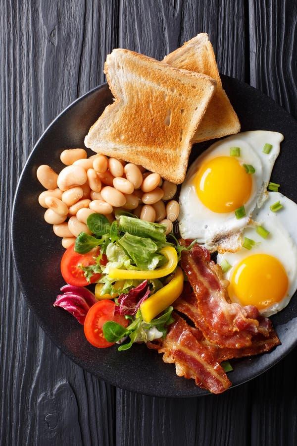 Φρέσκο πρόγευμα: τηγανισμένα αυγά με το μπέϊκον, φασόλια, φρυγανιά και vegetab στοκ εικόνες
