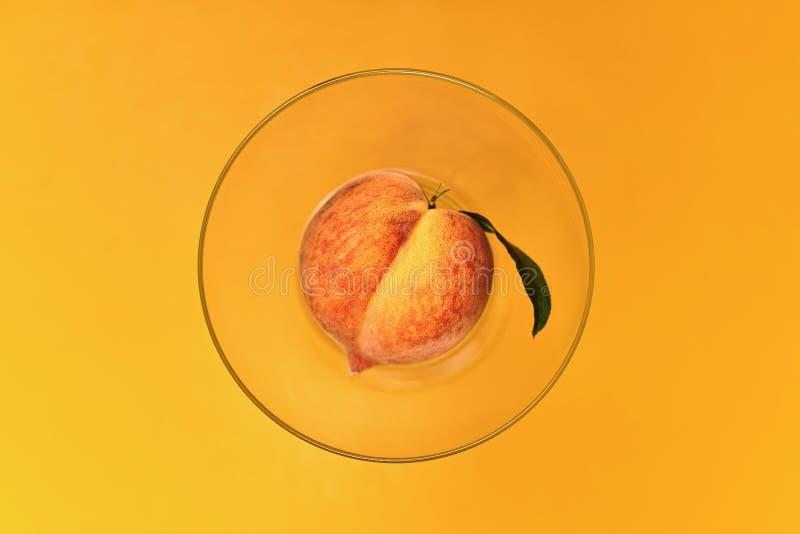 Φρέσκο ροδάκινο σε ένα διαφανές κύπελλο σε μια κίτρινη κορυφή στοκ εικόνα